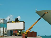 Forklift, crane in busy container port. Royalty Free Stock Image