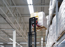 Forklift in a distribution warehouse. Huge distribution warehouse with boxes on high shelves Royalty Free Stock Photos