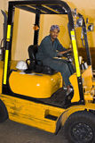 Forklift Driver. African male forklift driver inside transports goods inside a warehouse royalty free stock images