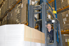 Forklift driver. In a forklift, carrying a large stack of flattened cardboard boxes Royalty Free Stock Photography