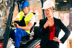 Forklift driver and supervisor at warehouse. Forklift driver with clipboard at warehouse of freight forwarding company, female super visor or dispatcher pointing Stock Photography