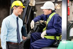 Forklift Driver Communicating With Supervisor. Young forklift driver communicating with supervisor at warehouse Royalty Free Stock Image
