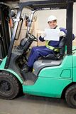 Forklift Driver Displaying Blank Placard. Portrait of forklift driver displaying blank placard Royalty Free Stock Photo
