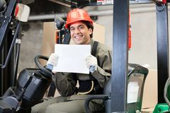 Forklift Driver Displaying Blank Placard. Portrait of happy young forklift driver displaying blank placard Stock Photos