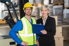 Forklift driver and his manager smiling at camera Royalty Free Stock Photo
