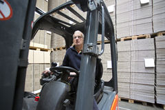 Forklift Driver. Inside a forklift, manipulating a joystick in a warehouse full of pallets empty, plano, cardboard boxes Royalty Free Stock Images