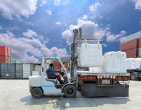 Forklift driver moving big bag to the truck at  yard. Royalty Free Stock Images