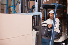 Forklift driver operating machine with boxes on it. In a large warehouse Royalty Free Stock Photo