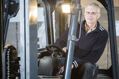 Forklift driver posing. Expreinced forklift driver is posing inside his forklift in a warehouse royalty free stock image