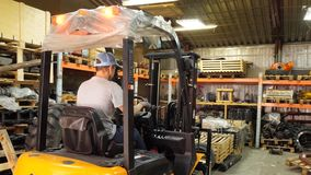 Forklift driver in protective vest driving forklift at warehouse of freight forwarding company. Man on the forklift. Drives into the garage stock photography