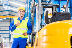 Forklift driver standing in manufacturing plant. Forklift driver standing proud in manufacturing plant Royalty Free Stock Photography