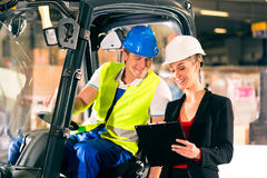 Forklift driver and supervisor at warehouse. Forklift driver and female super visor with clipboard at warehouse of freight forwarding company Stock Photo