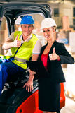 Forklift driver and supervisor at warehouse. Forklift driver and female super visor with clipboard at warehouse of freight forwarding company - thumbs up Stock Image