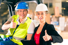 Forklift driver and supervisor at warehouse. Forklift driver and female super visor with clipboard at warehouse of freight forwarding company - thumbs up Royalty Free Stock Photo