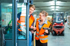 Forklift driver and supervisor at warehouse. Logistics Teamwork - forklift driver, Worker or warehouseman and his coworker with scanner at warehouse of freight Stock Photos