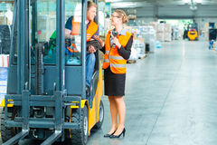 Forklift driver and supervisor at warehouse. Logistics Teamwork - forklift driver, Worker or warehouseman and his coworker with scanner at warehouse of freight Stock Images