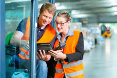 Forklift driver and supervisor at warehouse. Logistics Teamwork - forklift driver, Worker or warehouseman and his coworker with scanner at warehouse of freight Royalty Free Stock Photo