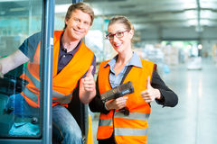 Forklift driver and supervisor at warehouse. Logistics Teamwork - forklift driver, Worker or warehouseman and his coworker with scanner at warehouse of freight Royalty Free Stock Images