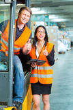 Forklift driver and supervisor at warehouse. Logistics Teamwork - forklift driver, Worker or warehouseman and his coworker with tablet computer at warehouse of Royalty Free Stock Photography