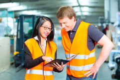 Forklift driver and supervisor at warehouse. Logistics Teamwork - Worker or warehouseman and his female coworker with tablet computer at warehouse of freight Royalty Free Stock Image