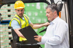 Forklift driver talking with his manager Stock Images
