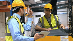 Forklift driver talking with his manager stock video