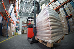 Forklift driver transporting sacks in warehouse Stock Image
