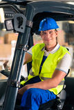 Forklift driver at warehouse of forwarding. Forklift driver in protective vest and forklift at warehouse of freight forwarding company, smiling stock images
