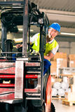 Forklift driver at warehouse of forwarding. Forklift driver in protective vest driving forklift at warehouse of freight forwarding company royalty free stock images