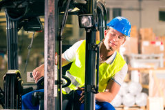 Forklift driver at warehouse of forwarding. Forklift driver in protective vest driving forklift at warehouse of freight forwarding company stock photo
