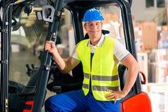Forklift driver at warehouse of forwarding. Forklift driver in protective vest and forklift standing at warehouse of freight forwarding company, smiling stock image