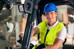 Forklift driver at warehouse of forwarding. Forklift driver in protective vest and forklift at warehouse of freight forwarding company, smiling stock photos