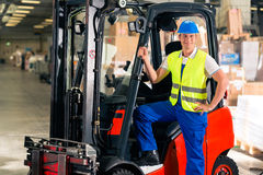Forklift driver at warehouse of forwarding. Forklift driver in protective vest and forklift standing at warehouse of freight forwarding company, smiling Royalty Free Stock Images