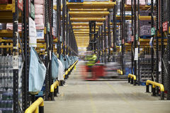 Forklift driving across an aisle in a warehouse, motion blur royalty free stock photos