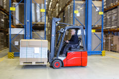 Forklift driving alongside a storage rack. Royalty Free Stock Photography