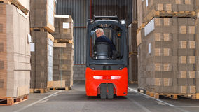 Forklift driving backwards. Expreinced forklift driver is driving his forklift backwards trough piled pallets with cardboardboxes stack on it royalty free stock images