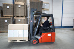 Forklift driving with a palet Royalty Free Stock Images