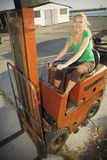 Forklift with female driver. Woman at work Stock Images