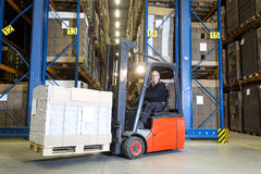 Forklift in front of storage racks. Forklift driver posing in front of a row with storage racks. On his fork he is transporting a pallet full of flat cardboard Royalty Free Stock Photography