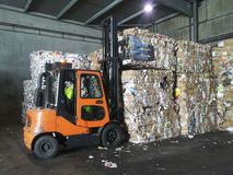 Forklift grabbing paper bales. Forklift grabbing paper recycled in Bales in a warehouse waste processing plant Royalty Free Stock Photography