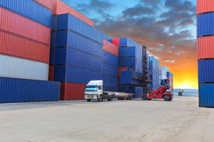 Forklift handling the container box at dockyard with beautiful s Stock Photos