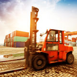 Forklift handling the container box at dockyard with beautiful s Stock Photography