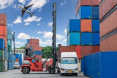 Forklift handling container box loading at docks with truck and. Airplane flying above for Logistic Import Export concept royalty free stock photo