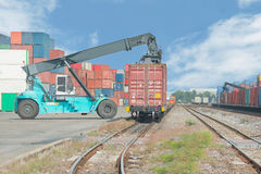Forklift handling container box loading to freight train Stock Image