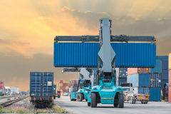 Forklift handling container box loading to freight train stock images