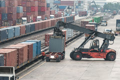 Forklift handling container box loading to freight train stock photography