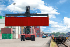 Forklift handling container box loading to freight train Royalty Free Stock Image