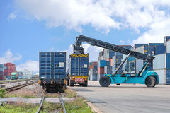 Forklift handling container box loading to freight train royalty free stock images