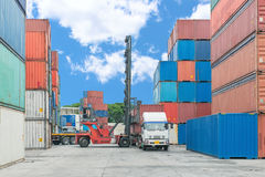 Forklift handling container box loading to truck Stock Photos