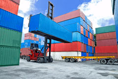 Forklift handling container box loading to truck i Royalty Free Stock Image